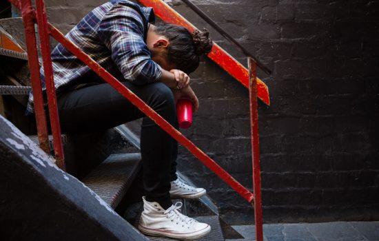 Drunk man sitting on staircase